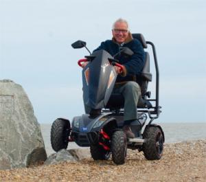 Older gentleman riding the vita monster on a sandy beach